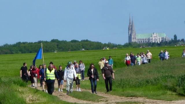 Randonneurs avec la cathédrale de Chartres dans les champs