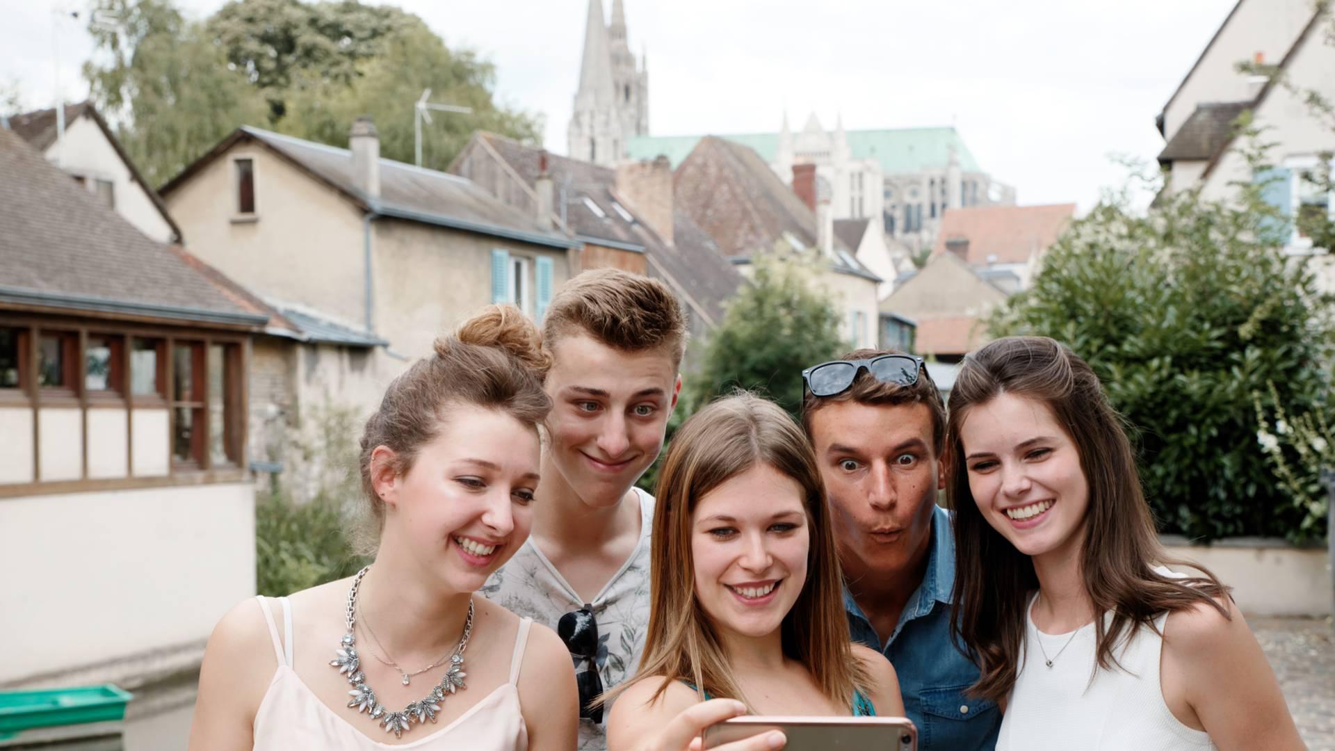 Jeunes faisant un selfie avec la cathédrale en fond