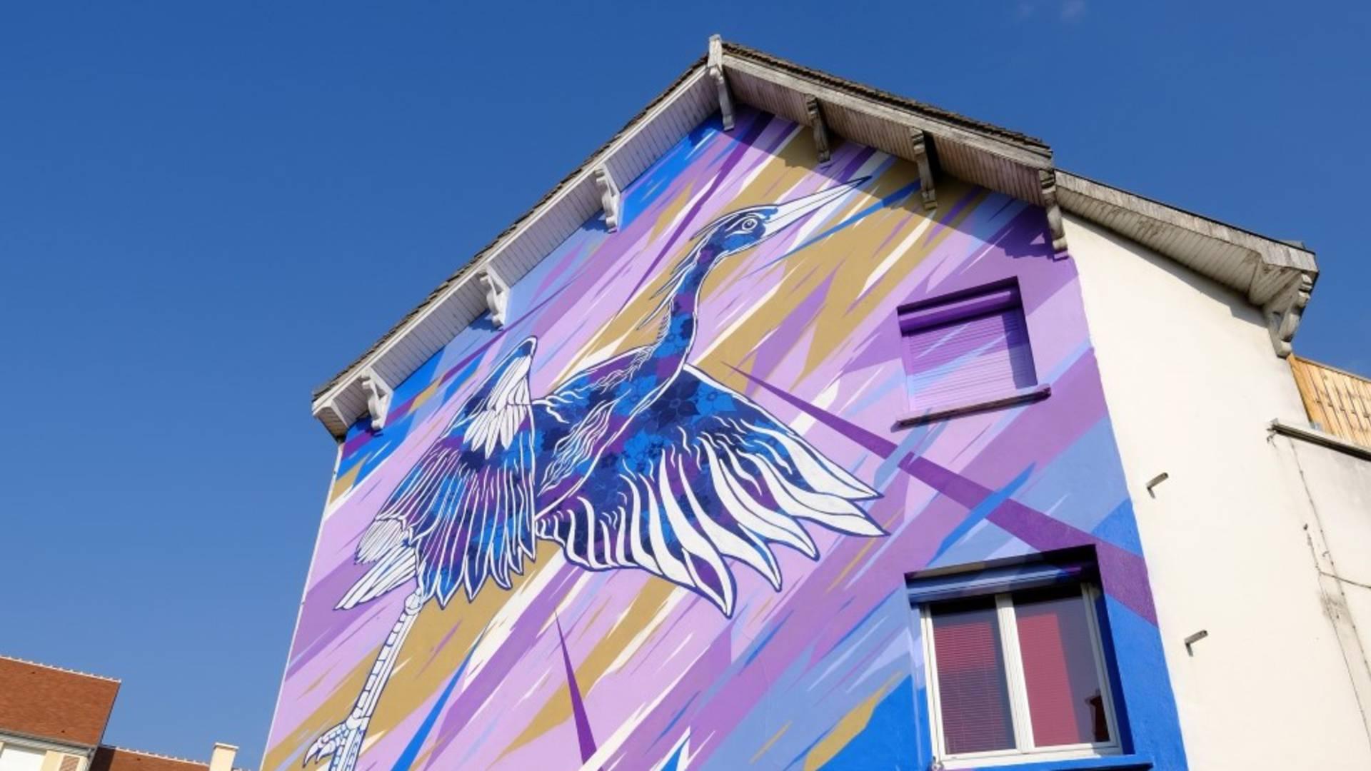 Héron cendré sur fond coloré sur une façade de bâtiment sur la place drouaise à Chartres