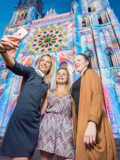 Jeunes femmes prenant un selfie devant la façade de la cathédrale lors de Chartres en lumières